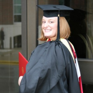 Smiling website author in cap and gown with diploma.