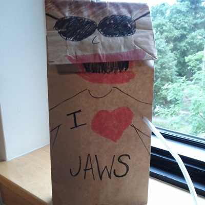 "A hand puppet made out of a brown paper bag holds a white pipe-cleaner ""cane"" and wears dark glasses and an I love JAWS t-shirt."